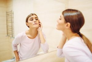 Cara menghilangkan jerawat -Woman looking on face at the mirror in bathroom