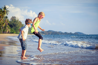 grosir baju anak murah Tanah Abang -Happy children playing on the beach at the day time.