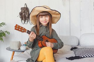 grosir baju anak di Bandung - Kid girl in hat playing ukulele at home