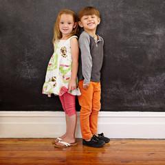 Little kids standing in front of blackboard - grosir baju anak di Bandung